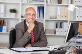 Podnikatel s rukou na bradě, sedící u stolu — Stock fotografie