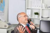 Gesturing businessman using telephone — Stock Photo