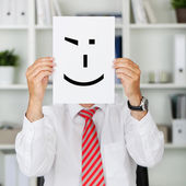 Businessman Holding Wink Smiley In Front Of His Face — Stock Photo