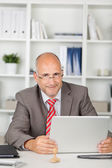 Friendly businessman sitting at desk with laptop — Stock Photo