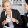 Businesswoman Having Coffee While Looking At Coworker — Stock Photo