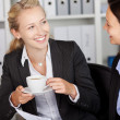 Stock Photo: Businesswoman Having Coffee While Looking At Coworker