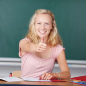 Female Teacher Showing Thumbs Up Sign At Desk — Stock Photo
