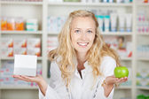 Female Pharmacist Holding Pill Box And An Apple — Stock Photo
