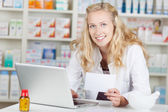 Pharmacist Holding Prescription Paper While Using Laptop At Coun — Stock Photo
