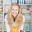Young Female Pharmacist With Piggy Bank — Stock Photo