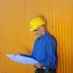 Architect Wearing Hardhat While Analyzing Blue Print — Stock Photo