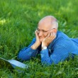 Businessman Chatting Online On Laptop While Lying On Grass — Stock Photo