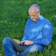 Man Holding Digital Tablet While Sitting On Grass — Stock Photo #25845081