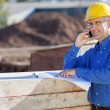Stock Photo: Architect Pointing At Blueprint While Using Mobile Phone At Site