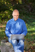 Businessman Using Laptop While Sitting On Rock At Park — Stock Photo