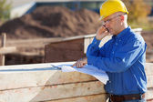 Architect Pointing At Blueprint While Using Mobile Phone — Stock Photo