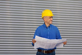 Architect Holding Blueprint While Looking Away Against Shutter — Stock Photo