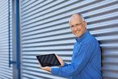 бизнесмен в отображение цифровых таблетки при опираясь на затвор — Стоковое фото