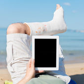 Man with plaster lying on the beach with Ipad — Stock Photo