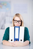 Businesswoman Holding Withe Binders At Desk — Stock Photo