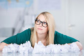 Businesswoman With Paper Balls On Desk Looking Away — Stock Photo