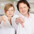 Pharmacists showing thumbs down — Stock Photo