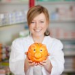 Pharmacist holding piggy bank — Stock Photo