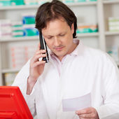 Pharmacist looking serious while on call — Stock Photo