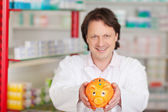 Pharmacist showing piggy bank — Stock Photo