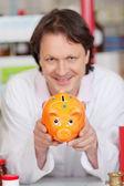 Confident pharmacist showing piggy bank — Stock Photo