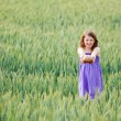 Young girl with bread in a wheatfield — Stock Photo
