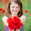 Beautiful little girl with red flowers — Stock Photo