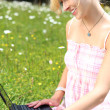 Woman using her laptop on green grass — Stock Photo