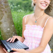 Vivacious woman using her laptop in nature — Stock Photo