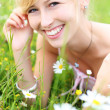 Beautiful smiling woman amongst spring flowers — Stock Photo