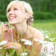 Laughing woman lying amongst white daisies — Stock Photo