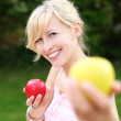 Beautiful woman offering an apple — Stock Photo