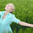 Stock Photo: Pretty womrejoicing in green field