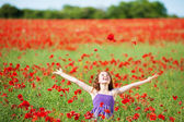 Laughing young girl in a poppy field — Stock Photo
