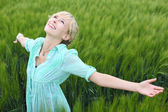 Pretty woman rejoicing in a green field — Stock Photo