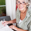Older woman wearing glasses working — Stock Photo