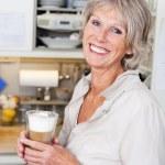 yaşlı kadın bir fincan kapuçino keyfi — Stok fotoğraf #25886427