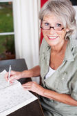 Older woman wearing glasses working — Foto Stock