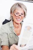 Elderly lady sitting reading the news — Stock Photo