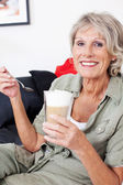 Senior woman with milky macchiato coffee — Stock Photo