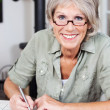 Smiling elderly woman doing a crossword puzzle — Stock Photo