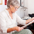 Trendy senior woman reading a newspaper — Stock Photo #25893841