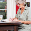 Senior woman writing notes at home — Stock Photo #25894109