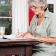 Senior woman writing notes at home — Stock Photo