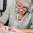 Senior woman completing a crossword puzzle — Stock Photo