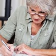 Stock Photo: Senior woman completing a crossword puzzle