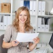 Businesswoman Holding Paper While Sitting On Chair At Office — Stock Photo