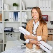 Stock Photo: Businesswoman Holding Blueprints At Office Desk