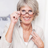 Happy senior lady wearing reading glasses — Stock Photo